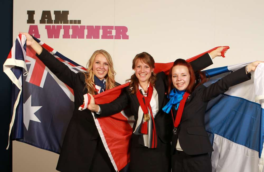 Three competitors celebrate at a WorldSkills competition